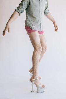 Pernas peludas de salto alto em calcinha rosa isoladas