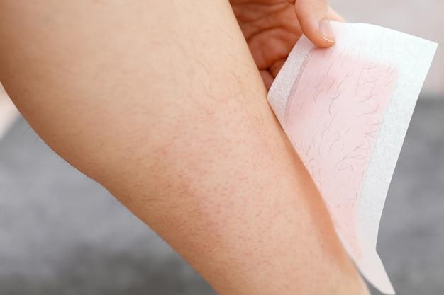 Pernas peludas. mulher usando listra de cera de abelha para raspar a perna. procedimento de depilação com cera, close up. conceito de remoção de cabelo.