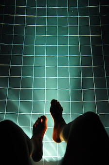 Pernas penduradas piscina luz incandescente