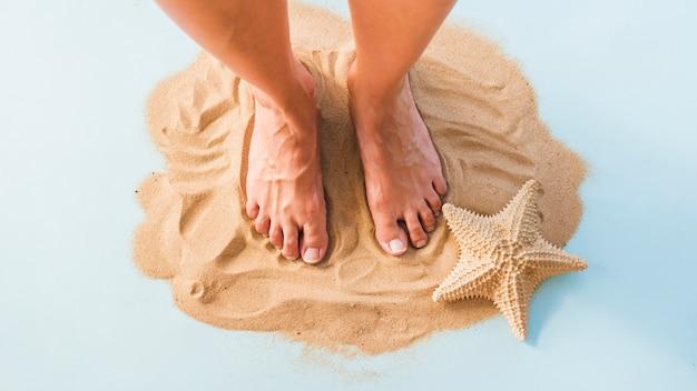 Pernas perto de grande estrela do mar na areia