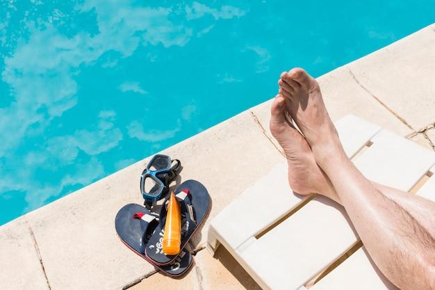 Pernas perto de óculos com loção e flip-flops perto da piscina