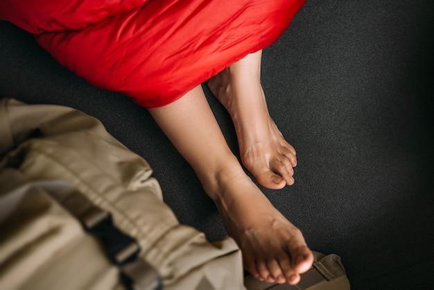 Pernas saindo do saco de dormir. pernas de mulher saindo de um saco de dormir vermelho. pernas saindo sob o cobertor vermelho. pernas sob o cobertor. um turista em um saco de dormir. copie o espaço