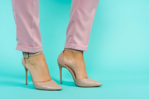 Pernas sensuais em sapatos marrons de salto alto em fundo azul