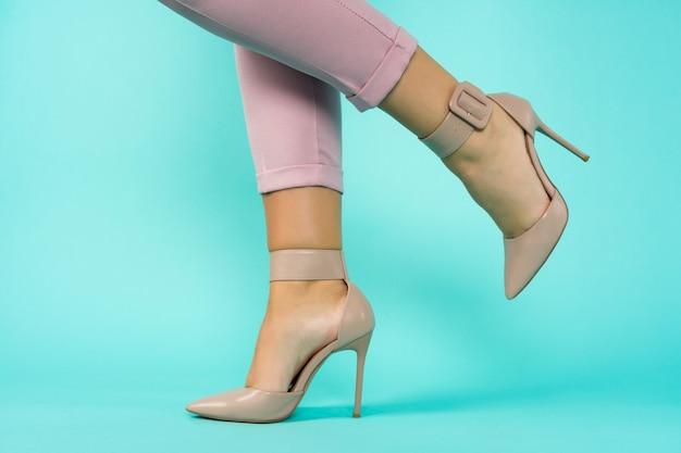 Pernas sexy em sapatos de salto alto marrons sobre fundo azul. - imagem