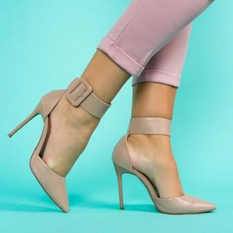 Pernas sexy em sapatos de salto alto marrons sobre fundo azul.
