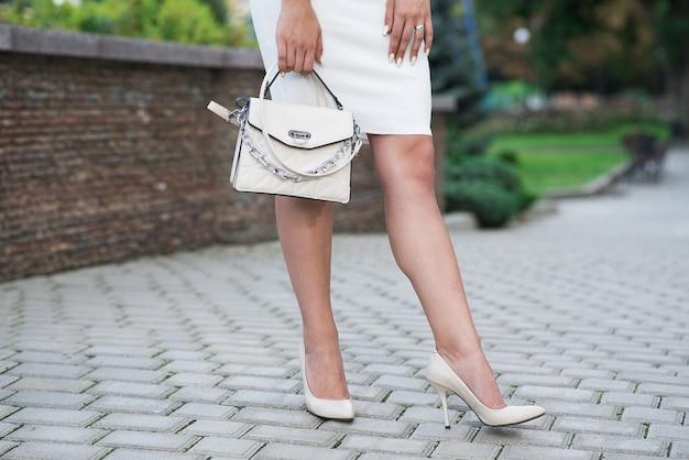 Pernas sexy femininas de uma garota caucasiana com uma bolsa. conceito de moda.