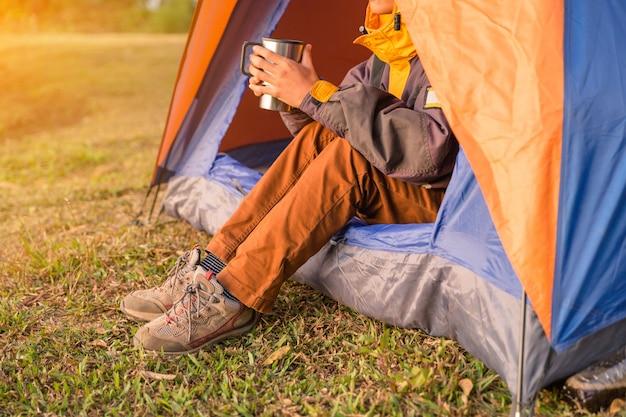 Pernas visíveis da tenda no parque de campismo em fundo de madeira selvagem