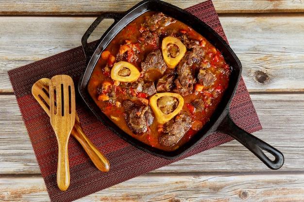 Pernil de boi cozido com legumes e vinho em ferro fundido. cozinha italiana.