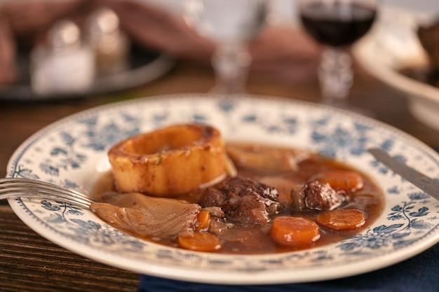 Pernil de carne bem cozido em molho de vinho servido em um prato antigo sobre uma mesa de madeira