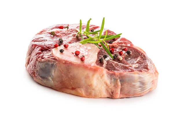 Pernil de carne crua com sal pimenta e alecrim isolado no fundo branco.