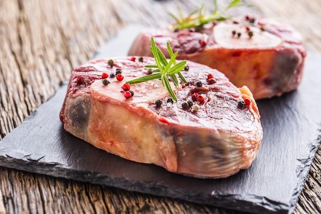 Pernil de carne crua de duas peças na placa de ardósia e mesa de madeira.