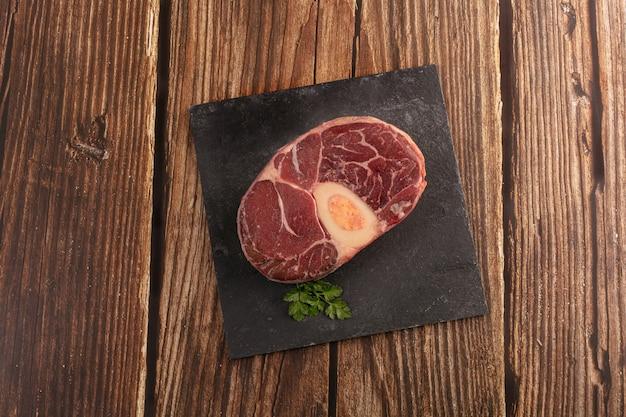 Pernil de carne crua para pot au feu em uma mesa de madeira
