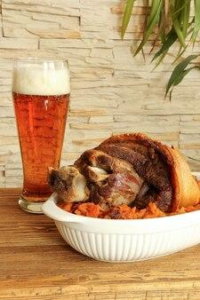 Pernil de porco assado com chucrute e cerveja em uma mesa de madeira