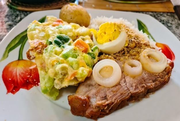 Pernil de porco assado, maionese de batata, cenoura, arroz branco e farofa