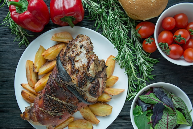 Pernil de porco frito com batatas servido em um prato branco de madeira escura. vista de cima.