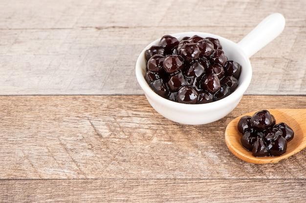 Pérola de tapioca, cobertura de bolha para chá ou outra bebida, em uma xícara, coloque sobre a mesa de madeira. copie o espaço