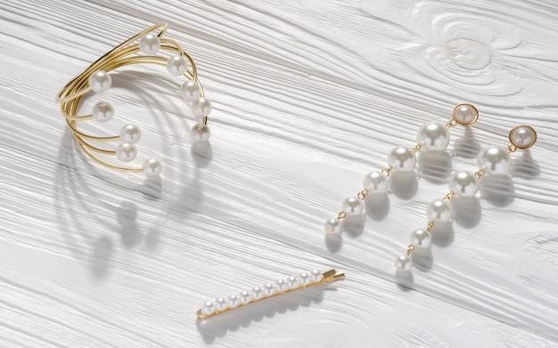Pérola dourada e ouro conjunto de pulseira, par de brincos e alfinete de cabelo em fundo branco de madeira