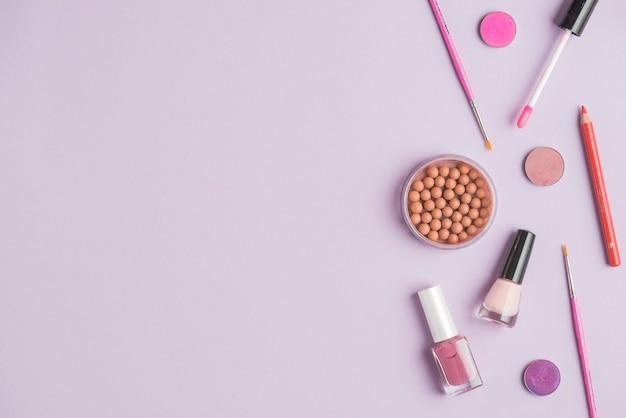 Pérolas bronzeadas com produtos cosméticos em fundo colorido