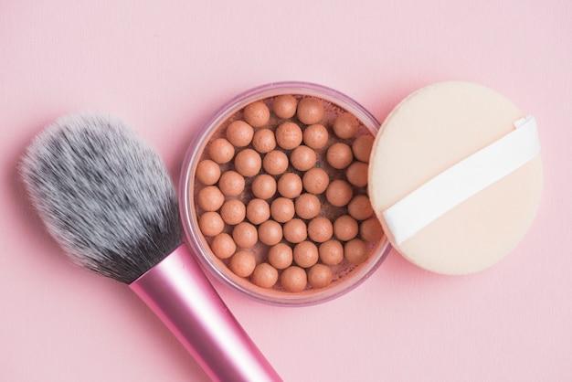 Pérolas bronzeadoras; esponja e pincel de maquiagem no pano de fundo rosa