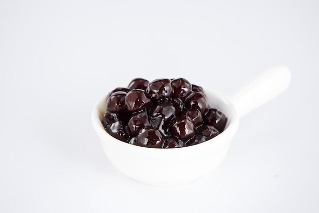 Pérolas negras. pérolas de tapioca fervidas para chá de bolhas em fundo branco. copie o espaço