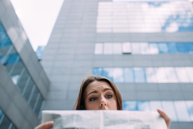 Perplexa, confusa, perplexa, perplexa, mulher lendo o conceito de jornal