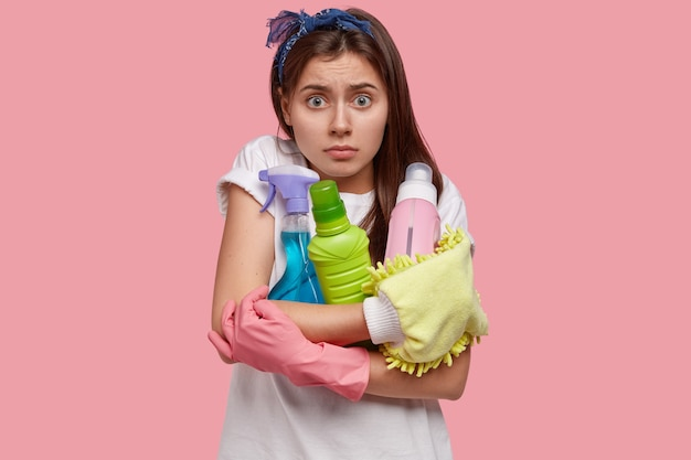 Perplexa surpresa linda mulher tem expressão assustada, segura detergentes para limpar, usa luvas de borracha, frustrada com muito trabalho