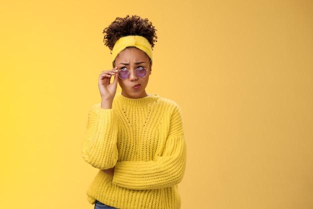 Perplexo, inseguro, elegante, mulher, afro-americana, criativa designer em óculos de sol de suéter com bandana, sorrindo, dobrando os lábios, tubo incerto, tenho dúvidas, franzindo a testa, olhar pensativo, não consigo decidir.