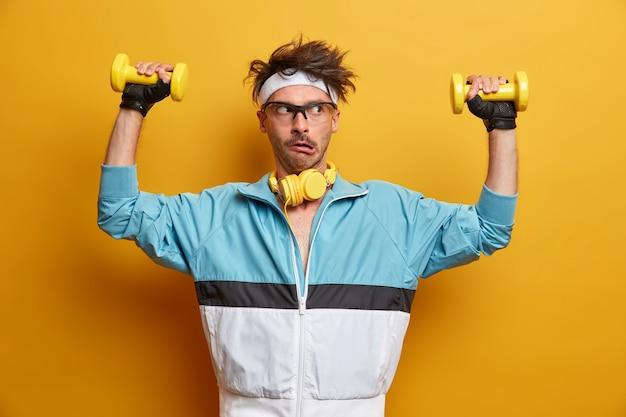 Perplexo jovem europeu treina músculos das mãos com halteres, faz todos os esforços para levantar peso, faz reabilitação física, faz exercícios para os braços, posa em casa ginásio vestido com roupas esportivas