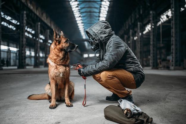 Perseguidor com máscara de gás e cachorro em prédio abandonado, sobreviventes na zona de perigo após a guerra nuclear.