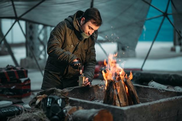 Perseguidor, homem cozinhando comida enlatada em chamas