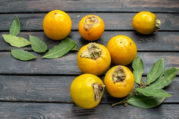 Persimmons frescos em uma mesa de madeira rústica com frutas maduras maduras