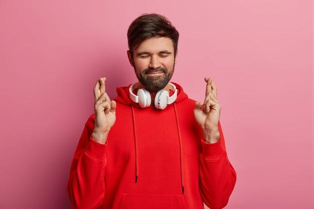 Persistente homem barbudo bonito fica de pé com dedos cruzados, fecha os olhos e espera pelo momento especial, usa moletom vermelho e fones de ouvido estéreo em volta do pescoço, espera resultados, posa sozinho