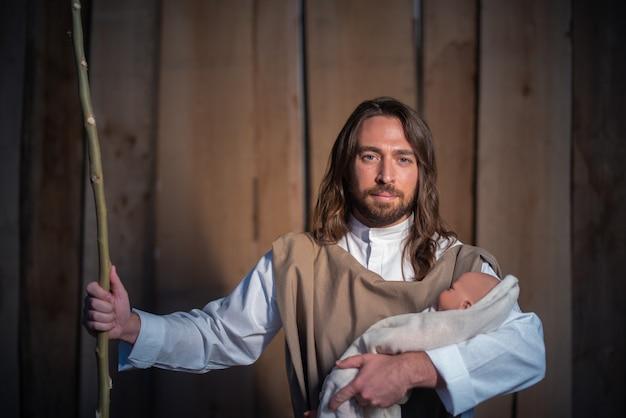 Personagem bíblica de josé segurando o bebê de jesus em um berço