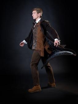 Personagem da história steampunk, jovem atraente em um elegante casaco longo, aventureiro faz um gesto épico. cavalheiro inteligente em estilo vitoriano. terno retro vintage, jovem atraente