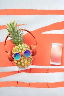 Personagem de abacaxi hipster de óculos e fones de ouvido no fundo de papel listrado