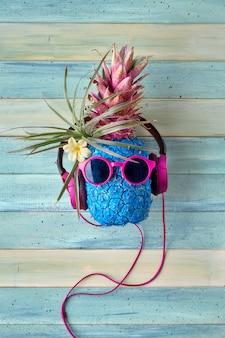 Personagem de abacaxi hipster em fones de ouvido e óculos de sol roxos ouve a música