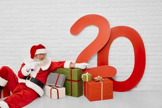 Personagem de natal sênior, sentada no chão com caixas de presente