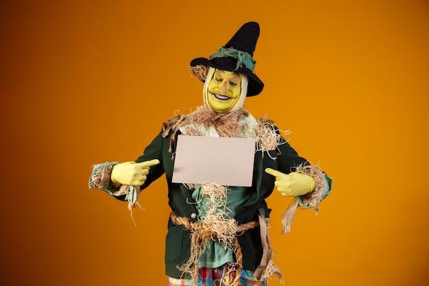 Personagem espantalho da festa junina em parede amarela