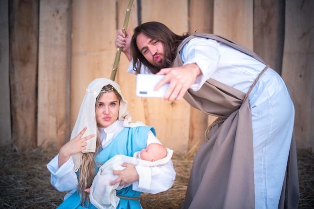 Personagens bíblicos tirando selfie enquanto brincam no presépio