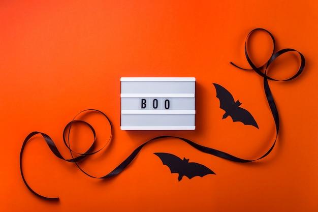 Personagens de halloween preto e acessórios em uma superfície laranja brilhante