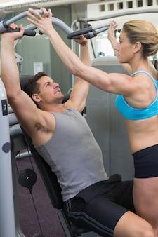 Personal bodybuilders treinador usando máquina de peso