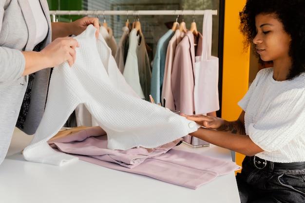 Personal shopper no escritório com cliente mostrando calças