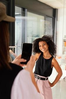 Personal shopper no escritório com cliente tirando fotos