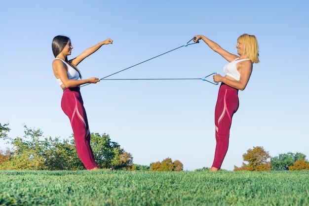 Personal trainer de esportes e fitness, vestida com roupas esportivas, treina uma mulher loira sênior com estilo de vida saudável ao ar livre, realizando alongamentos com elásticos sorrindo feliz durante o exercício
