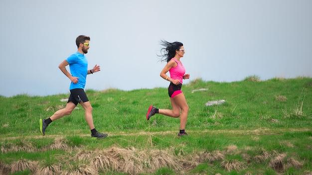 Personal trainer enquanto treina sua mulher desportiva para correr nos prados