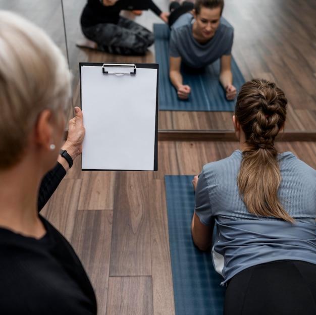 Personal trainer feminina ajudando seu cliente por cima do ombro