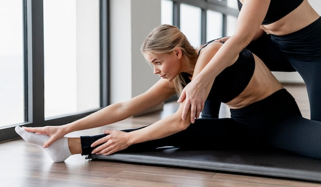 Personal trainer feminina e alongamento do cliente