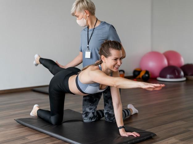 Personal trainer feminina e cliente trabalhando em ambientes fechados
