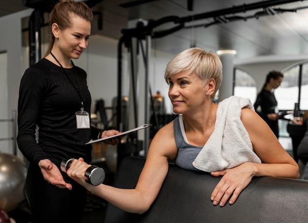 Personal trainer feminina e seu cliente usando halteres