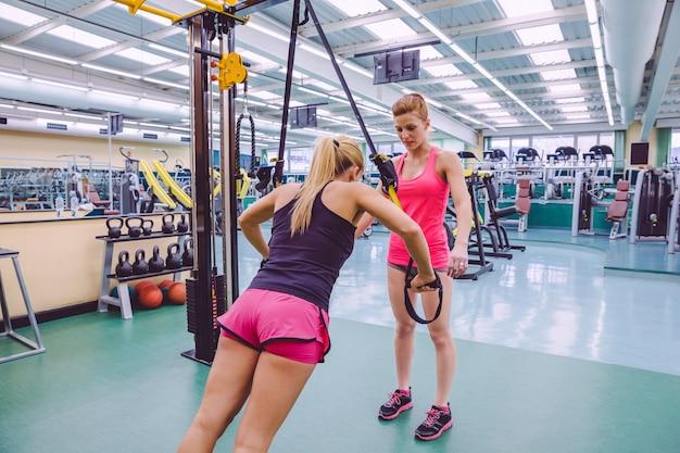 Personal trainer feminina ensinando para mulheres em um treinamento de suspensão rígida com alças de fitness em uma academia